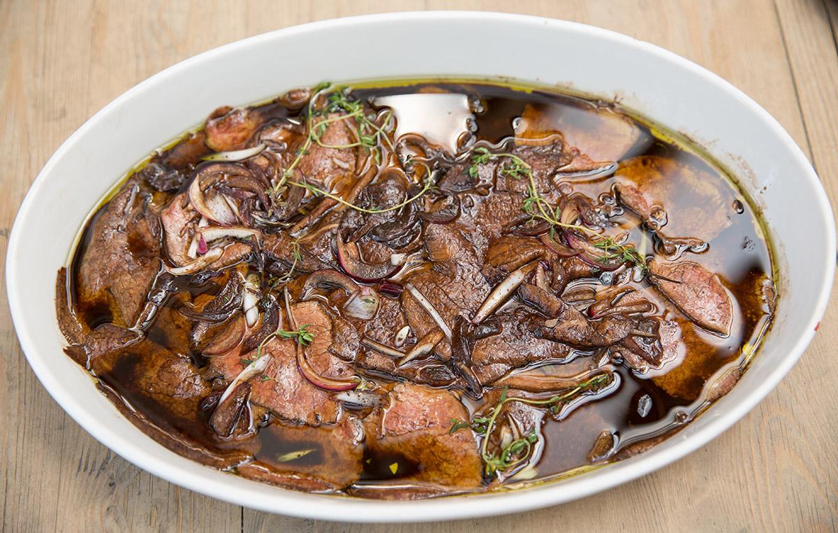 Отварная телятина, замаринованная в пряных травах, оливковом масле и бальзамическом уксусе, поджидает на столе закусок при входе.